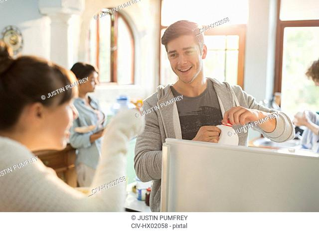 Young adults enjoying breakfast in apartment kitchen