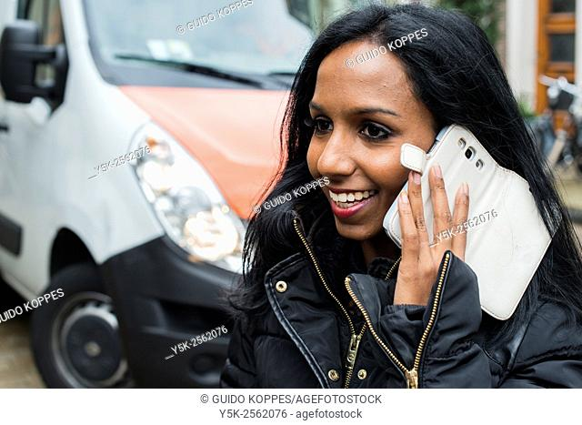 Tilburg, Netherlands. Young, attractive female having a conversation in the streets, using her smartphone