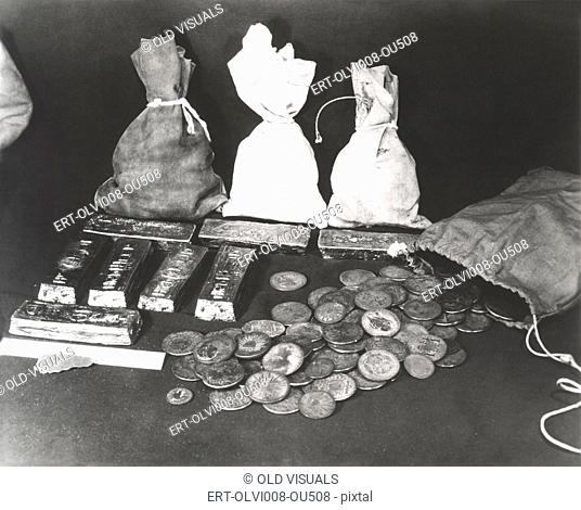 Gold coins and bars laid out on table