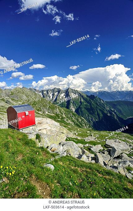 Red bivouac with granite mountains in background, bivouac Molteni, Sentiero Roma, Bergell range, Lombardy, Italy