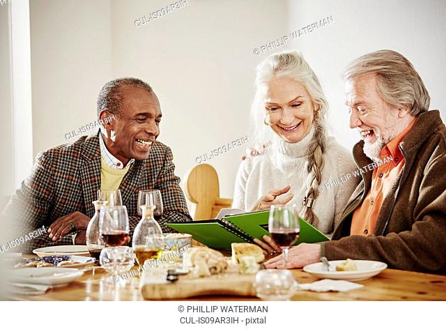 Senior friends looking at book at dinner