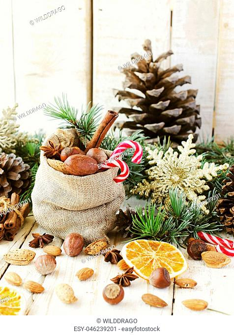 New Year or Christmas composition with walnuts, mulled wine, hazelnuts, pistachios in canvas bags with fir branches and cones