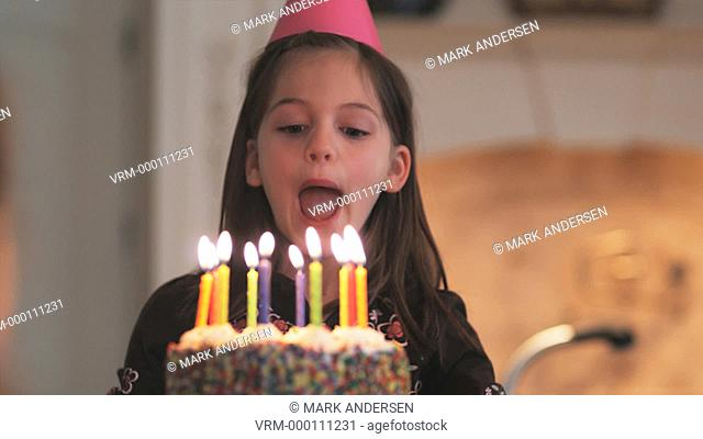 little girl blowing out the candles on her birthday cake