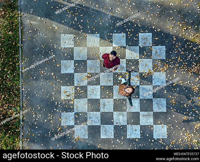 Carefree woman with arms outstretched standing by man on chessboard painted on asphalt