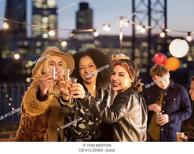 Portrait enthusiastic young adult friends toasting champagne flutes at nighttime rooftop party