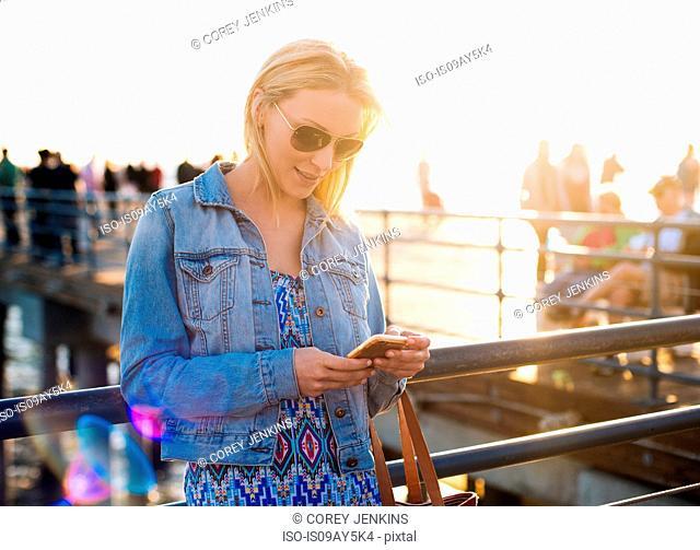 Young woman reading smartphone texts on pier, Santa Monica, California, USA