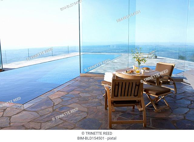 Table and chairs near infinity pool overlooking scenic view