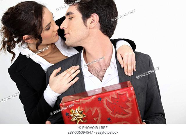 Couple with Christmas present about to kiss