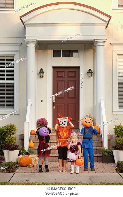 Children covering face with Jack O' Lantern bucket in front of house