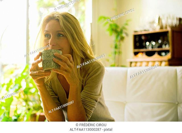 Mature woman drinking coffee at home