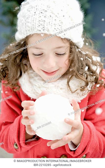 Girl wearing winter clothing holding a snowball