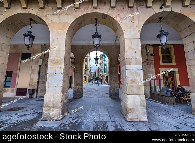 San Bernardo Street seen from passage under building on Plaza Mayor - Main Square in Gijon in the autonomous community of Asturias in Spain