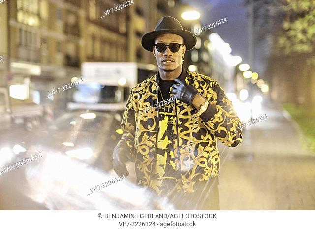 mid shot of fancy man at city street at night, wearing stylish outfit, car lights, traffic, cool attitude, in Munich, Germany