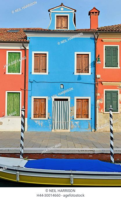 Blue house with red neighbours on the island of Burano in the Venice lagoon, where no two adjacent houses are the same colour. Boat in front