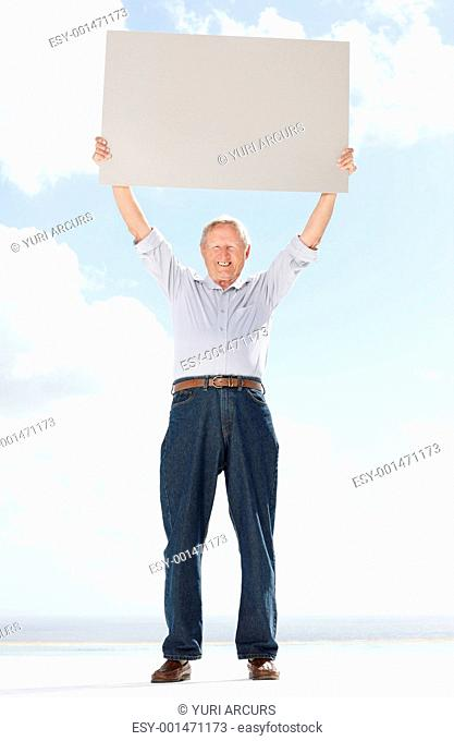 Portrait of a retired old man holding an empty sheet against the sky