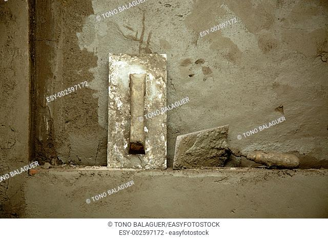 dirty grunge cement trowel hand tools on fresh mortar wall