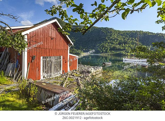 red shed on the seashore of Balestrand, Norway, typical wooden hut with view to the Sognefjorden