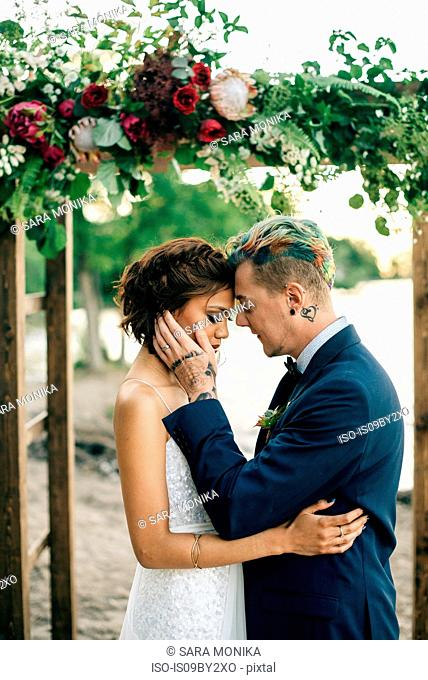 Romantic bride and groom face to face on lakeside