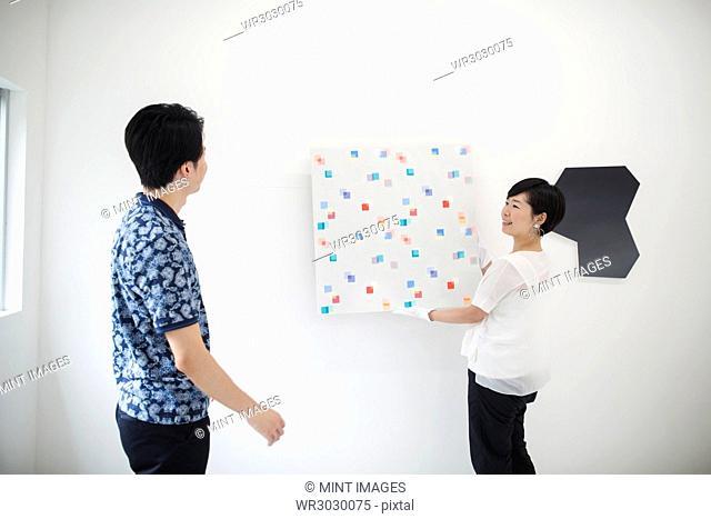 Man wearing blue shirt watching woman hang modern painting on white wall in art gallery