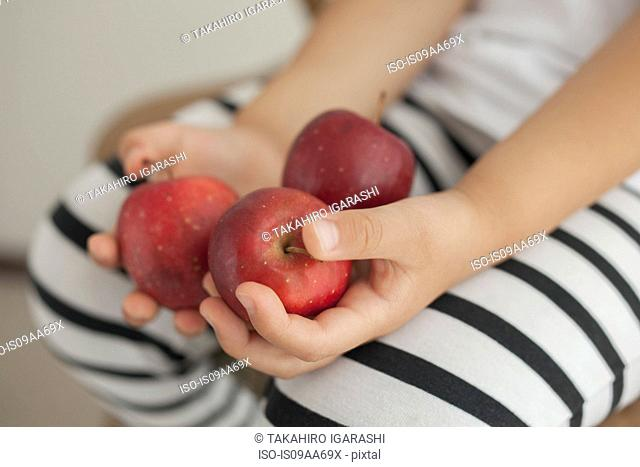 Girl holding three red apples