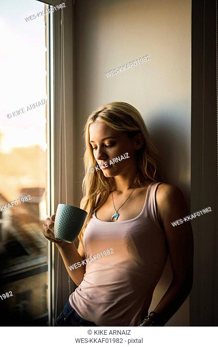 Blond young woman holding coffee mug at the window