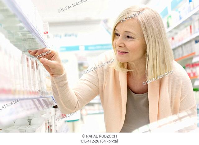 Customer reaching for box on shelf in pharmacy