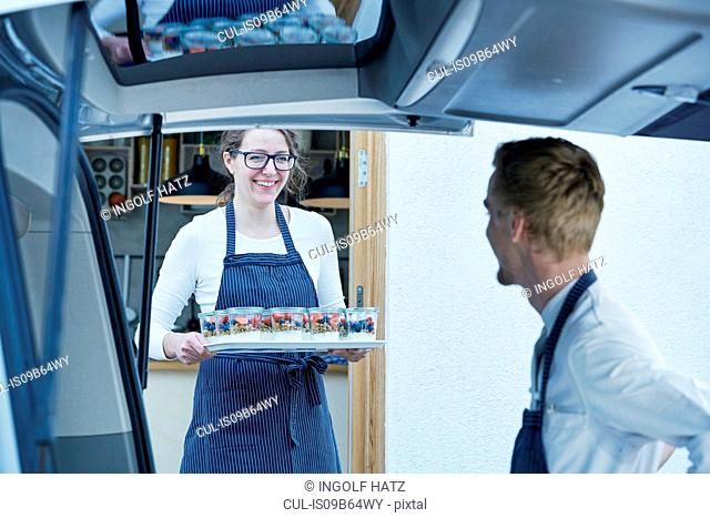 Caterers loading vehicle with prepared food