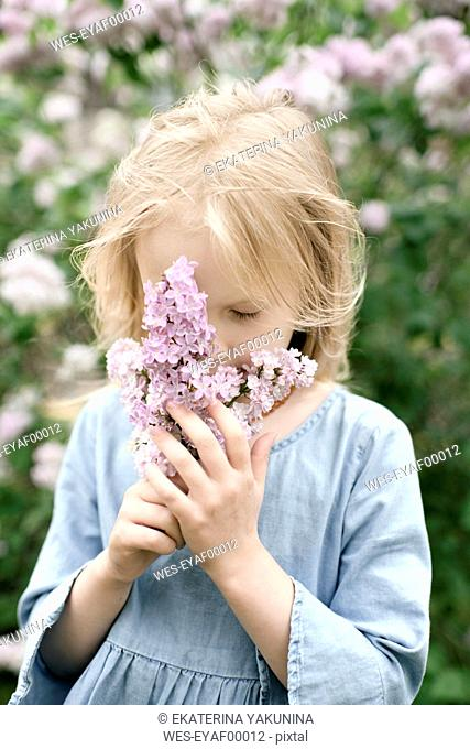 Portrait of smiling girl with lilac blossoms, sniffing