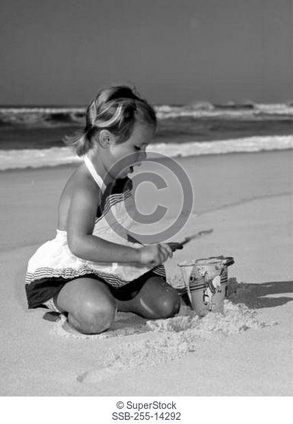 Girl playing on beach with toy bucket
