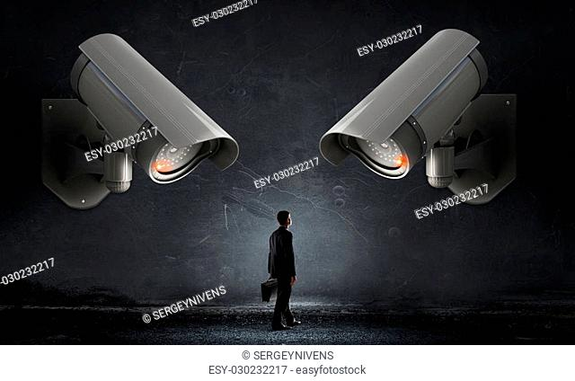 Young scared man in room under CCTV camera control