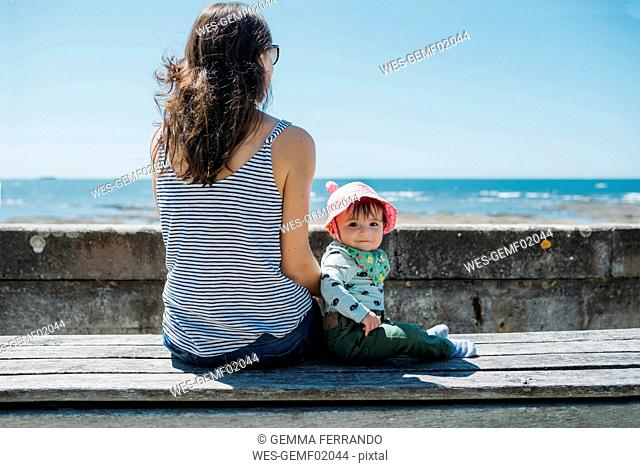France, mother and baby girl sitting on a bench at beach promenade