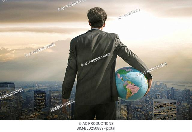 Caucasian businessman holding globe overlooking cityscape