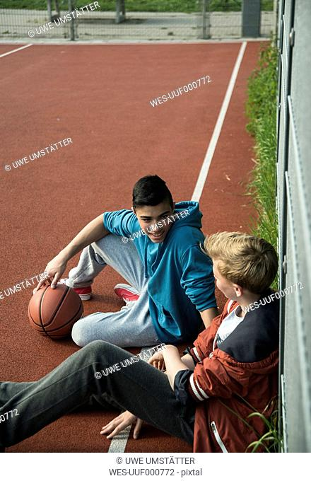 Two boys with basketball leanaing against fence