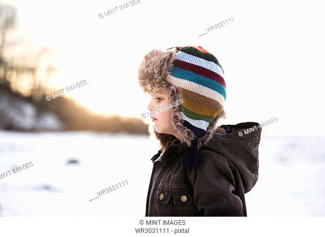 Young boy wearing stripey furry hat standing in the snow