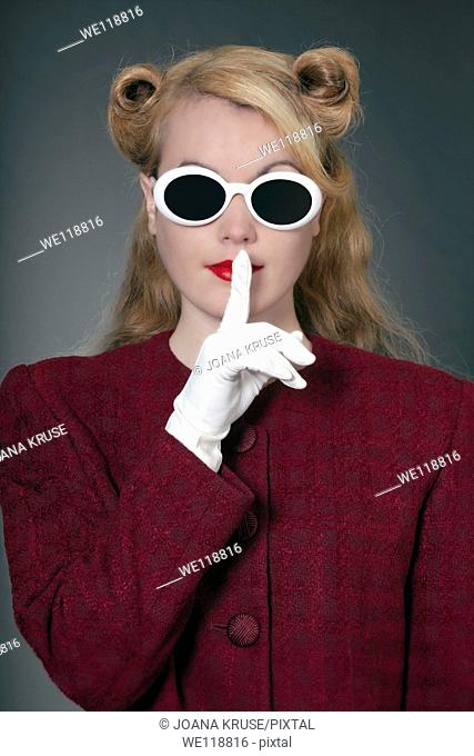 a woman in a vintage blazer with vintage sunglasses in 50s style with her finger on her lips