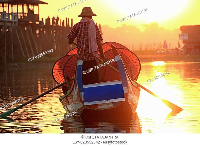Burmese boatman and buddhist novice sitting in boat
