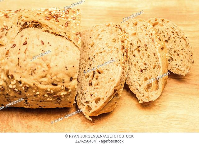 Home made bread loaf with seeds and grains cut into slices on wooden chopping block. Since sliced bread
