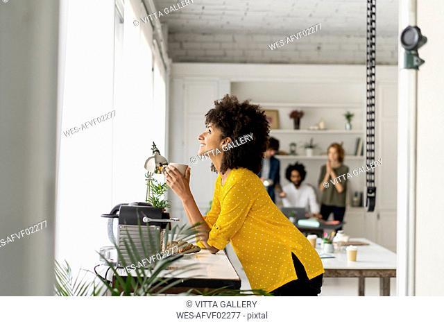 Woman enjoying her coffe break in the office
