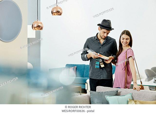 Couple in furniture store looking at color samples