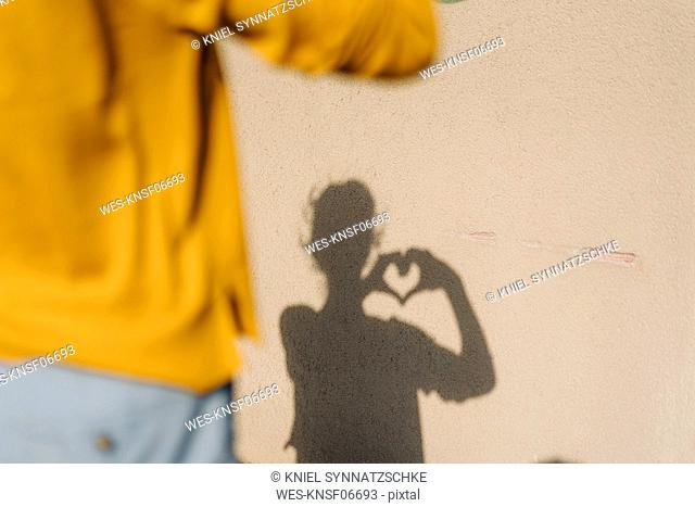 Shadow of a woman shaping a heart with her hands