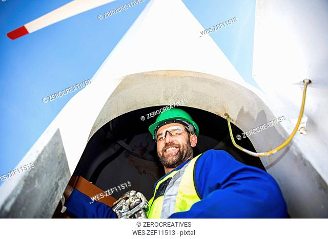 Engineer inspecting wind turbine, using wrench