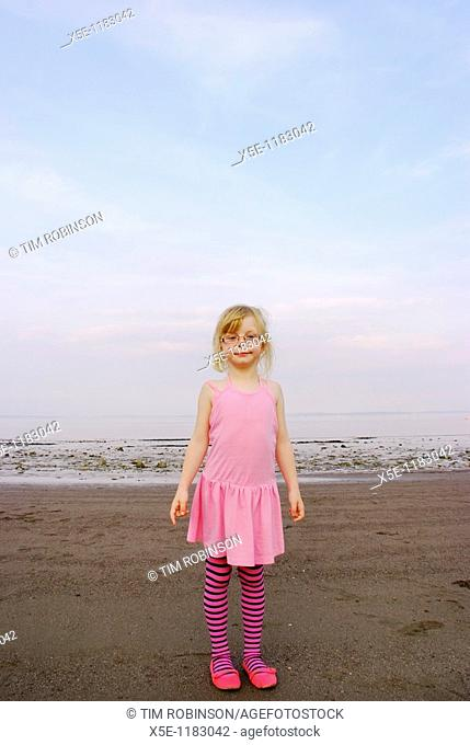 Portrait of 7 year girl wearing pink dress and tights at beach looking at camera
