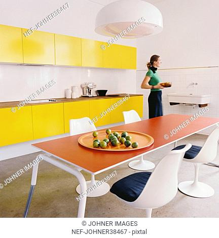 Woman with plate standing in the kitchen