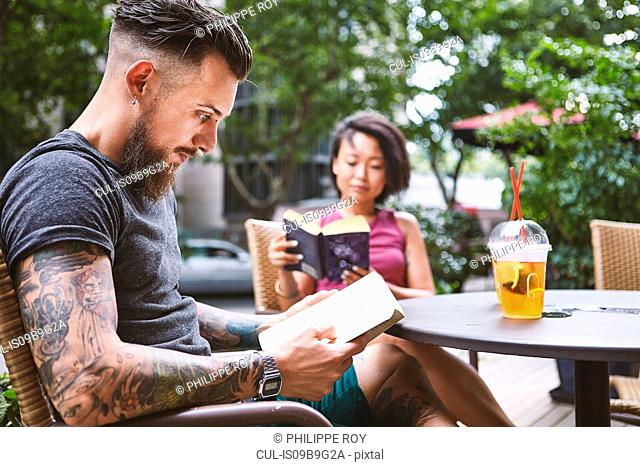 Multi ethnic hipster couple reading books at sidewalk cafe, Shanghai French Concession, Shanghai, China