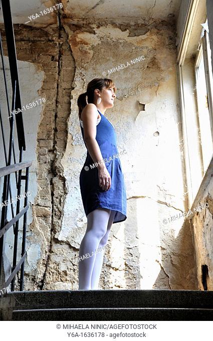 Young woman standing in ruined corridor looking through window