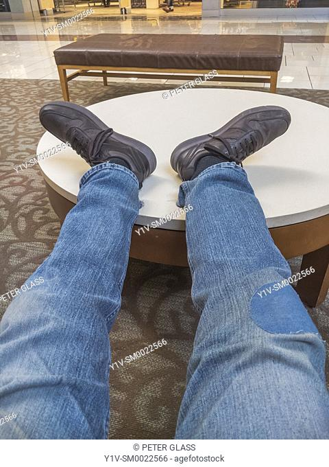 Man's feet and legs stretched out on a round table in an office building lobby