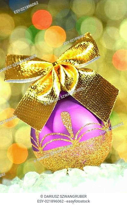 christmas decoration, violet Christmas ball with golden bow in bokeh background