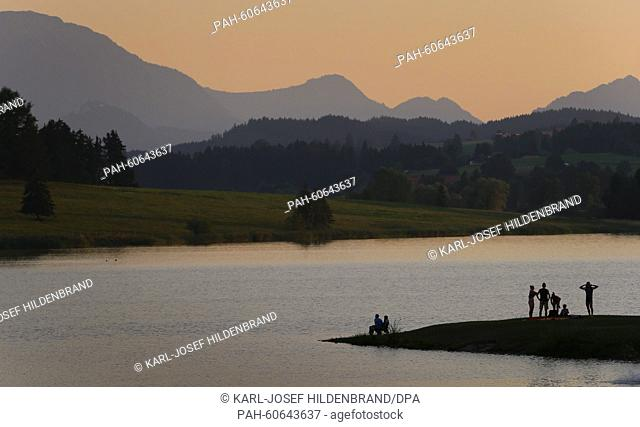 Bathers enjoy the view of the Allgaeu Alps in the evening light, on the banks of Illasberg lake near Rosshaupten, Germany, 7August 2015