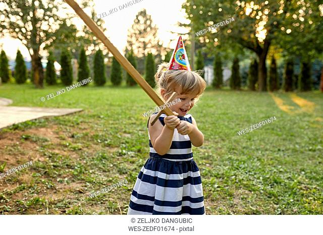Happy little girl wearing party hat and holding wooden sword in garden