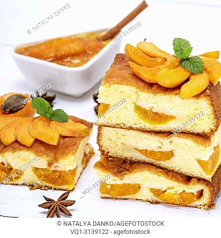 baked apricot biscuit cake, square pieces on a white wooden board